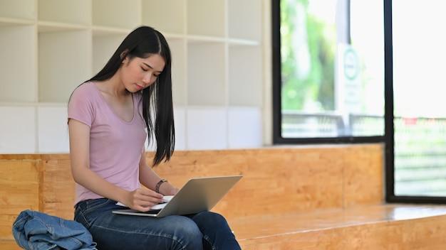 Het jonge boek van de vrouwenlezing met laptop computer in bibliotheekruimte.