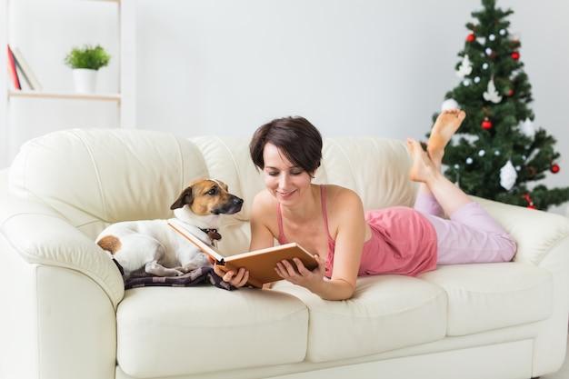 Het jonge boek van de vrouwenlezing thuis dichtbij kerstboom