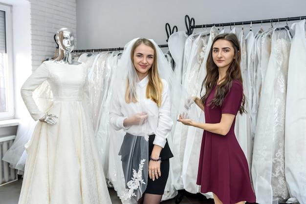 Het jonge bruid stellen met sluier in huwelijkssalon