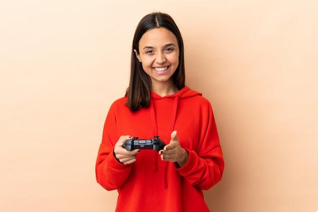Het jonge brunette gemengde rasvrouw spelen met een videospellingscontrolemechanisme over het toejuichen van de muur