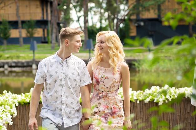 Het jonge charmante blondemeisje flirt en met een kerel in de tuin. lovestory van een verliefd paar