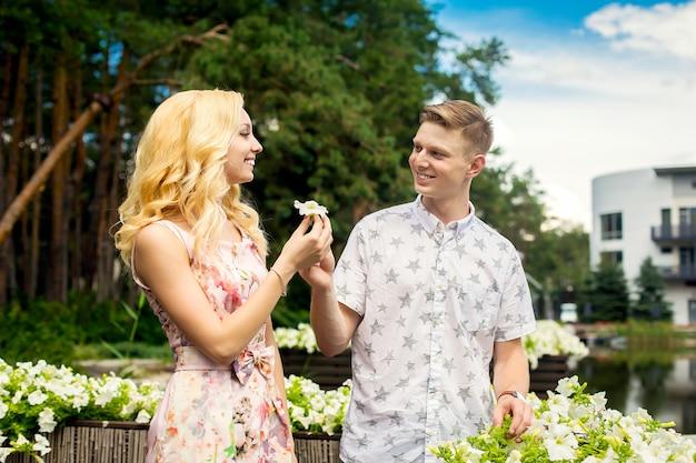 Het jonge charmante blondemeisje flirt en met een kerel in de tuin. lovestory van een verliefd paar.