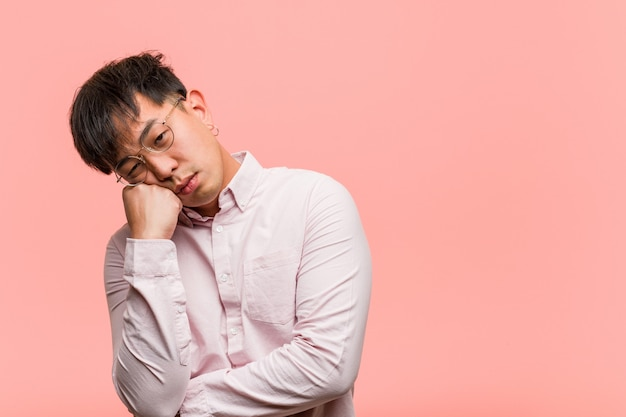 Het jonge chinese mens denken aan iets, kijkend aan de kant