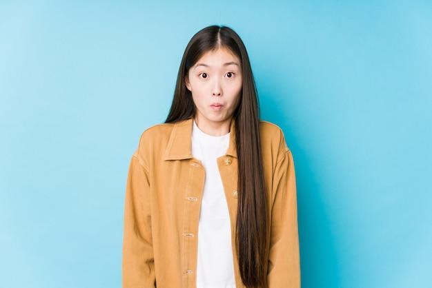 Het jonge chinese vrouw stellen in blauw