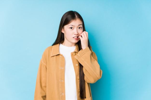 Het jonge chinese vrouw stellen in een blauwe geïsoleerde muur het bijten vingernagels, zenuwachtig en zeer bezorgd.