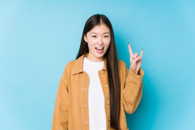 Het jonge chinese vrouw stellen in een blauwe geïsoleerde muur het tonen van een hoornengebaar als revolutieconcept.