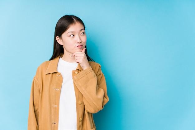 Het jonge chinese vrouw stellen in een blauwe geïsoleerde muur zijdelings het kijken met twijfelachtige en sceptische uitdrukking.