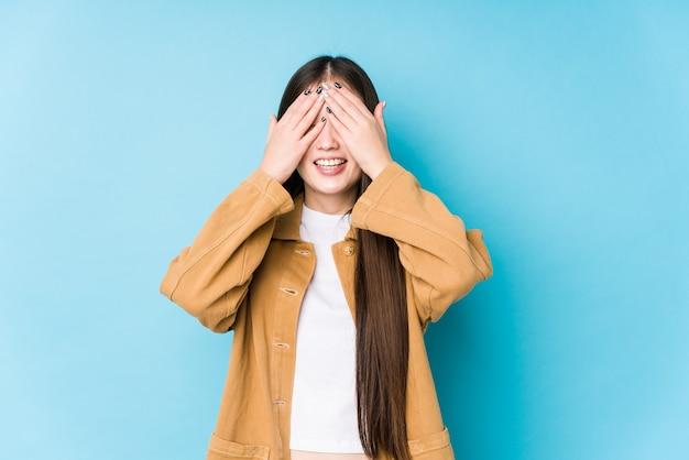 Het jonge chinese vrouw stellen in een blauwe geïsoleerde ruimte behandelt ogen met handen, glimlacht in het algemeen wachtend op een verrassing.