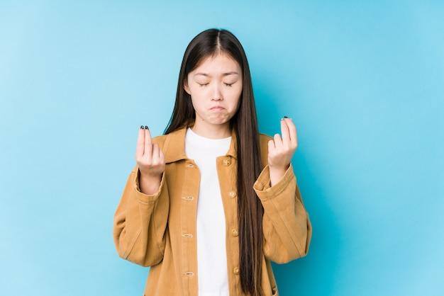 Het jonge chinese vrouw stellen in een blauwe muur die aantoont dat zij geen geld heeft.