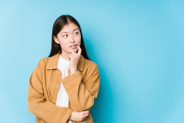 Het jonge chinese vrouw stellen in een blauwe ontspannen muur het denken over iets bekijkend een lege ruimte.