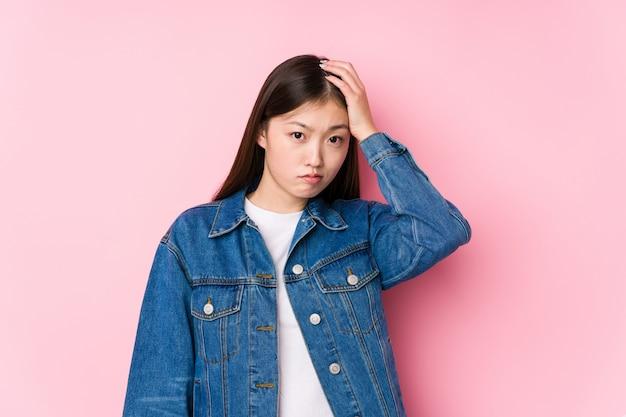 Het jonge chinese vrouw stellen in een roze geïsoleerde muur het geschokt zijn, heeft zij belangrijke vergadering herinnerd.