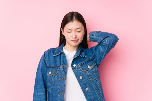 Het jonge chinese vrouw stellen in een roze geïsoleerde muur lijdend aan halspijn toe te schrijven aan sedentaire levensstijl.