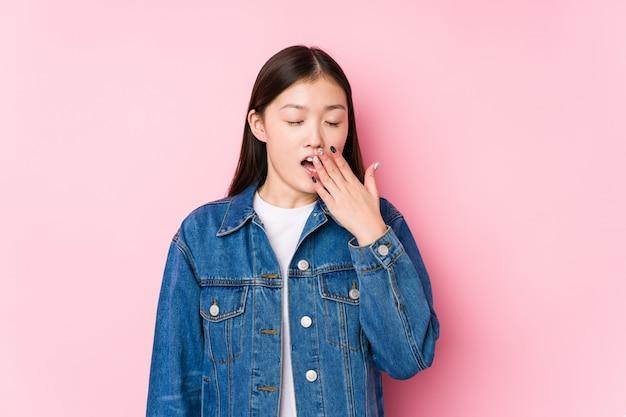 Het jonge chinese vrouw stellen in een roze muur geïsoleerde geeuw tonend een vermoeid gebaar die mond behandelen met hand.