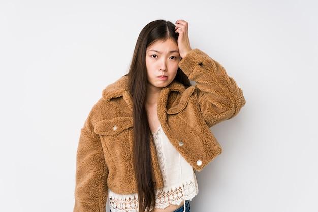 Het jonge chinese vrouw stellen in een witte geïsoleerde muur het geschokt zijn, heeft zij belangrijke vergadering herinnerd.