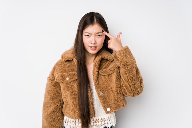 Het jonge chinese vrouw stellen in een witte geïsoleerde muur het tonen van een teleurstellingsgebaar met wijsvinger.