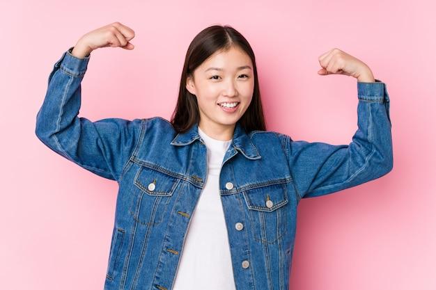 Het jonge chinese vrouw stellen in geïsoleerd roze die sterktegebaar met wapens tonen, symbool van vrouwelijke macht