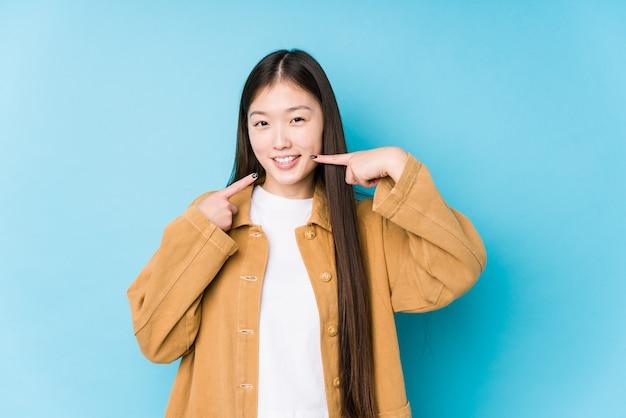 Het jonge chinese vrouw stellen op een blauwe geïsoleerde achtergrond glimlacht, die vingers richten op mond.