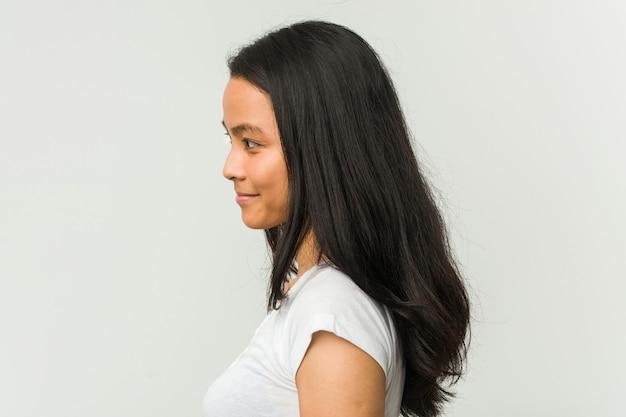 Het jonge chinese vrouw stellen op een witte muur