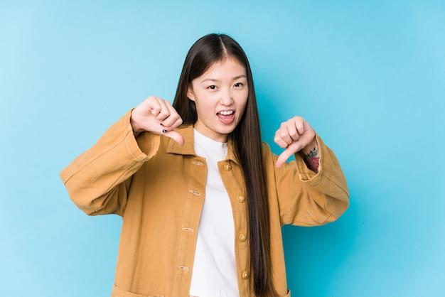 Het jonge chinese vrouw stellen op geïsoleerd blauw met duim neer en het uiten van afkeer.