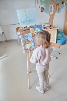 Het jonge creatieve gelukkige meisje trekt een beeld in lichte, moderne klas