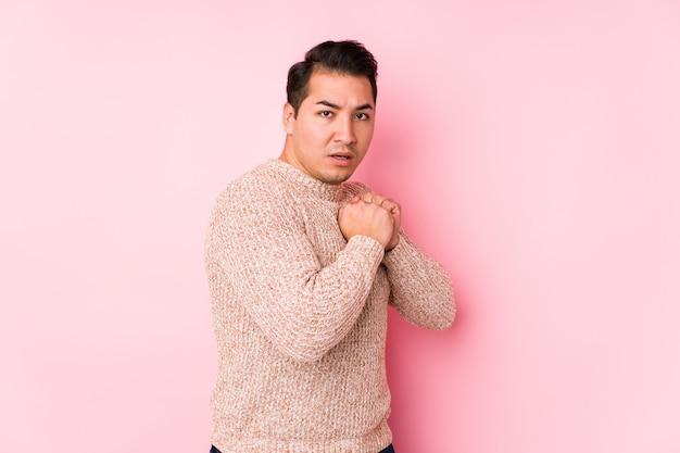 Het jonge curvy mens stellen in een roze geïsoleerde muur bang en bang.