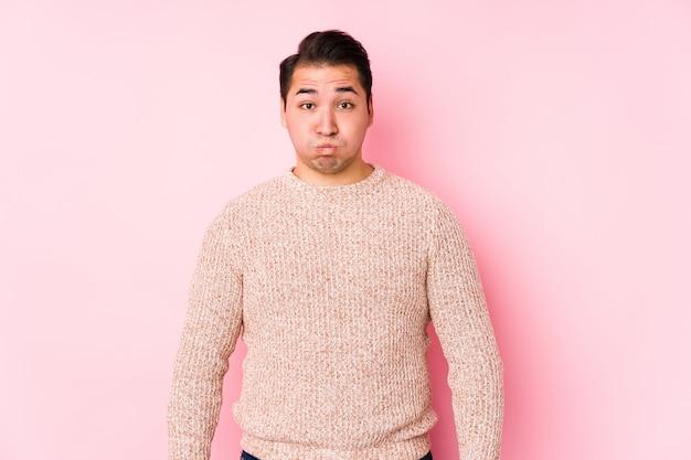 Het jonge curvy mens stellen in een roze geïsoleerde muur blaast wangen, heeft uitdrukking vermoeid. gelaatsuitdrukking concept.