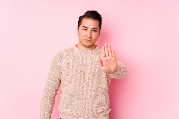 Het jonge curvy mens stellen in een roze geïsoleerde muur status met uitgestrekte hand die eindeteken tonen, die u verhinderen.