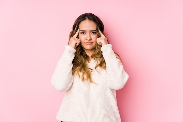 Het jonge curvy vrouw stellen in een roze geïsoleerde muur concentreerde zich op een taak, houdend wijsvingers die hoofd richten.