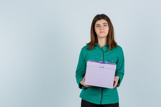 Het jonge de giftdoos van de meisjesholding in beide dient groene blouse, zwarte broek in en kijkt ontevreden. vooraanzicht.