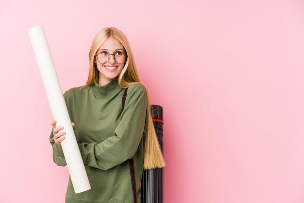 Het jonge de student van de blondearchitectuur glimlachen zeker met gekruiste wapens