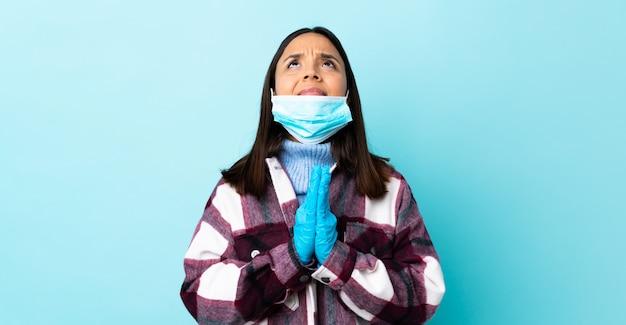 Het jonge donkerbruine gemengde rasvrouw beschermen met een masker en handschoenen over blauwe muur houdt palm samen