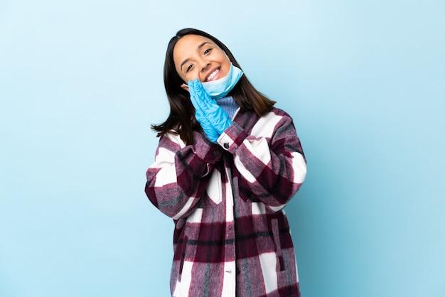 Het jonge donkerbruine gemengde rasvrouw beschermen tegen het coronavirus met een masker en handschoenen over geïsoleerde blauwe muur houdt palm samen. persoon vraagt iets