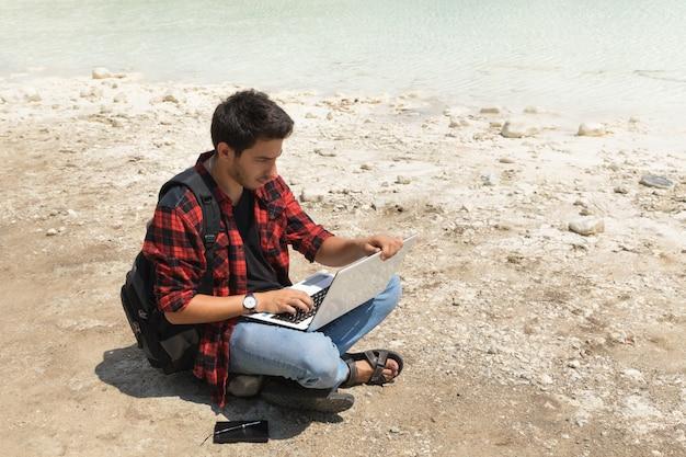 Het jonge donkerbruine mannetje in jeans en overhemd werkt bij een computer terwijl het zijn aan de aard.