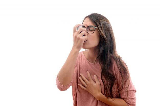 Het jonge donkerbruine meisje lijdt aan astma dat met een geïsoleerde inhalator inhaleert.