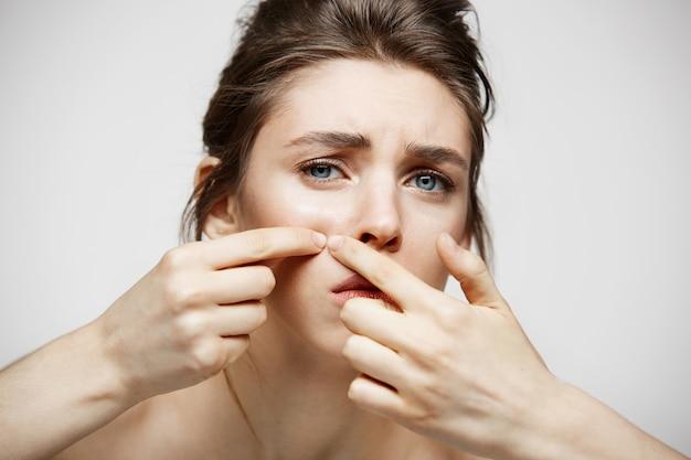Het jonge donkerbruine meisje ontevreden van haar gezichtshuid van de probleemacne over witte achtergrond. gezondheidskosmetiek en huidverzorging.