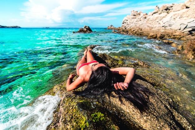 Het jonge donkerbruine meisje ontspannen in het water