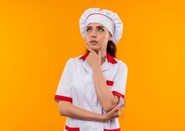 Het jonge doordachte kaukasische kokmeisje in eenvormige chef-kok legt hand op kin die op oranje muur met exemplaarruimte wordt geïsoleerd