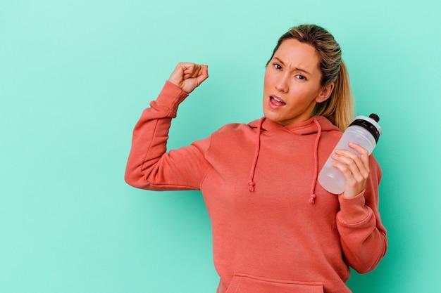 Het jonge drinkwater van de sportvrouw dat op blauwe wallraisingvuist na een overwinning wordt geïsoleerd