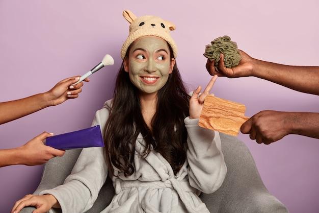 Het jonge duizendjarige meisje past een organisch gezichtsmasker toe op het gezicht na het nemen van een douche