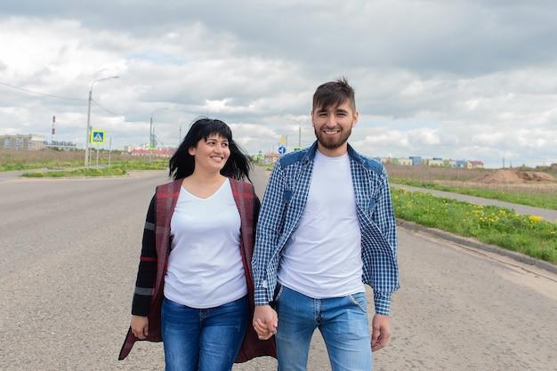 Het jonge en gelukkige paar dat over straat loopt