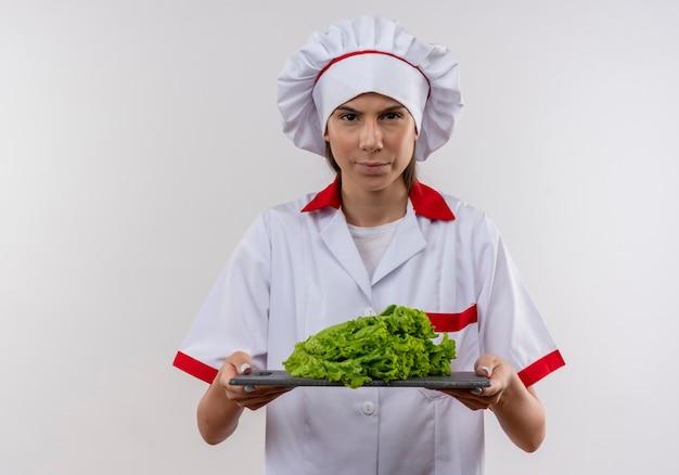 Het jonge ernstige kaukasisch kokmeisje in eenvormige chef-kok houdt salade op scherpe raad op wit met exemplaarruimte