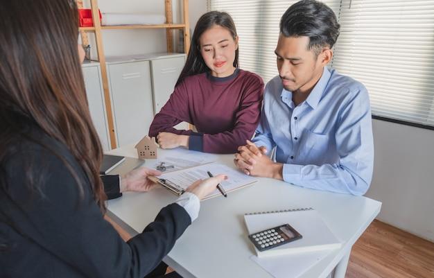 Het jonge familiepaar luistert naar de makelaar in onroerend goed legt uit over de koopovereenkomst van het huisleningcontract
