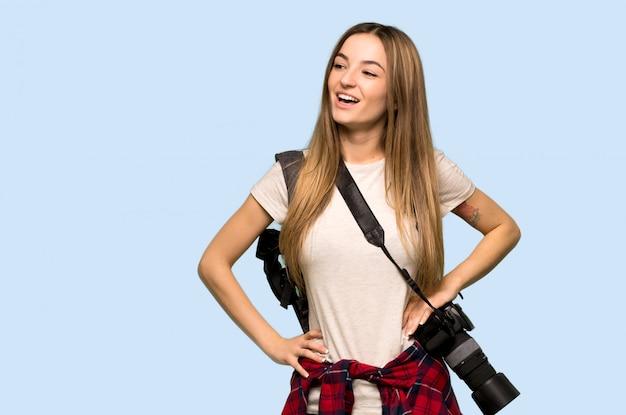 Het jonge fotograafvrouw stellen met wapens bij heup en lachend op geïsoleerde blauwe muur
