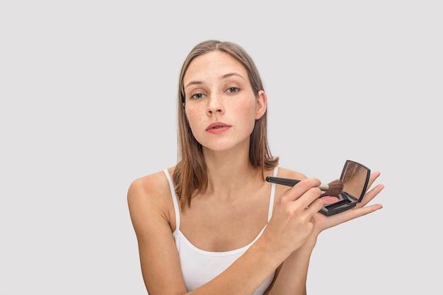 Het jonge freckled model stelt. ze houdt pallete oogschaduwen vast en gebruikt daarvoor een borstel. model ziet eruit. zij is cool.
