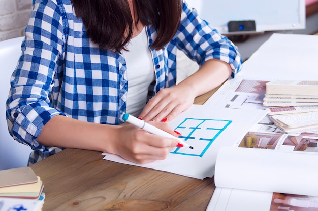 Het jonge freelancer binnenlandse ontwerper werken ontwikkelt nieuw flatproject in ontwerpstudio. de vrouwelijke meisjes vrouwelijke vergadering met ontmoet bureau met speld op schetstekeningen en ontwerpen van nieuw project
