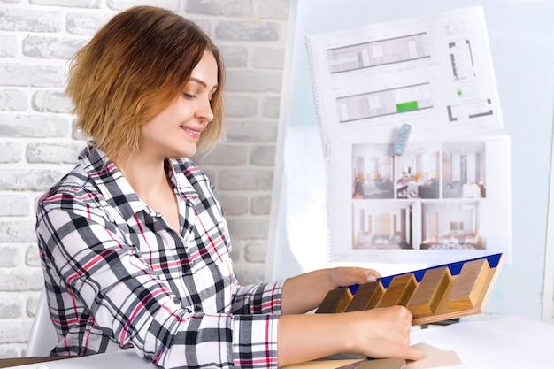 Het jonge freelancer binnenlandse ontwerper werken ontwikkelt nieuw flatproject in ontwerpstudio. vrouwenmeisje vrouwelijke ontmoeting met pin-up schetstekeningen, ontwerpen en houten maket van nieuw project