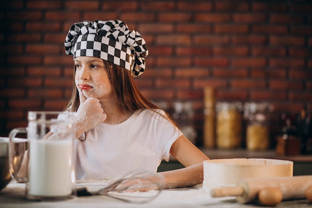 Het jonge gebakje van het meisjebaksel bij de keuken voor ontbijt