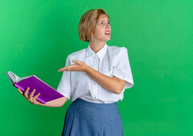 Het jonge geërgerde blonde russische meisje houdt en wijst op boek die kant bekijken die op groene achtergrond met exemplaarruimte wordt geïsoleerd