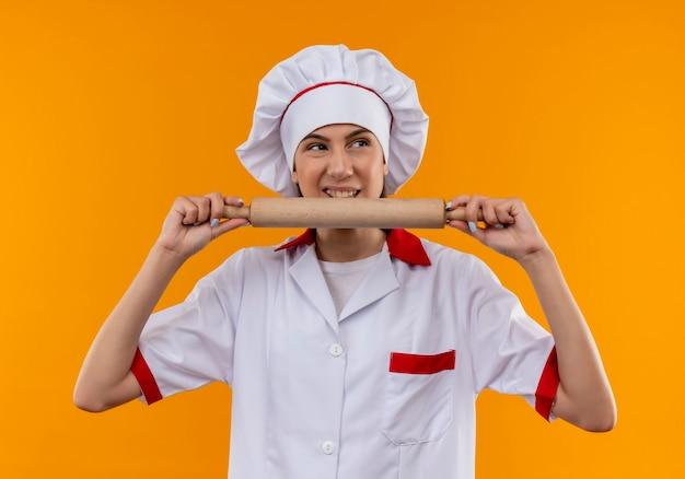 Het jonge geërgerde kaukasisch kokmeisje in eenvormige chef-kok houdt en beweert deegroller te bijten die op oranje achtergrond met exemplaarruimte wordt geïsoleerd