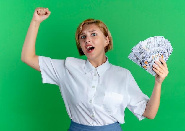 Het jonge geïrriteerde blonde russische meisje houdt geld met opgeheven vuist die op groene achtergrond met exemplaarruimte wordt geïsoleerd
